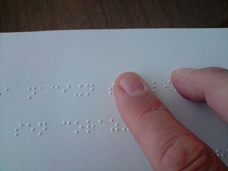 A_person_reading_a_braille_book