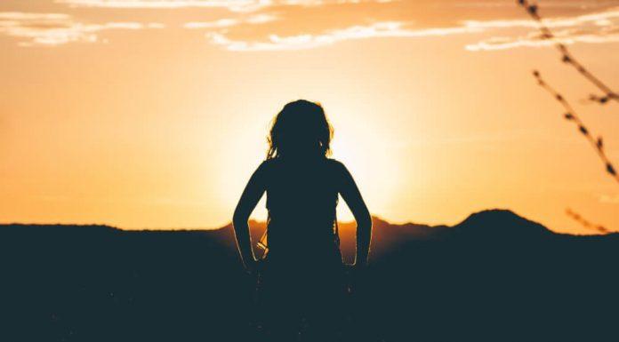 Silhouette d'une femme de dos avec soleil