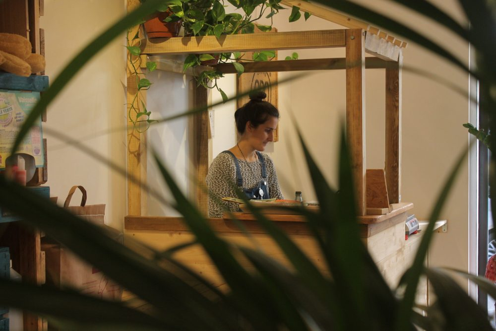 Andrea Silva derrière le comptoir de sa nouvelle boutique Misstinguette en salopette