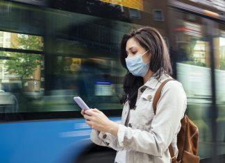 Femme avec un masque qui attend le bus